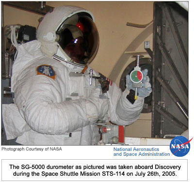 Astronaut holding the Rex Gauge SG-5000 Durometer.